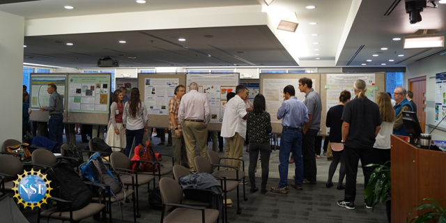 Photo of a meeting room with scientific posters hanging on the walls. About a dozen researchers are clustered around the posters talking with one another about their research.